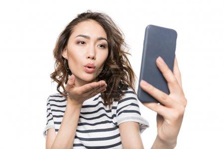Photo pour Femme soufflant baiser tout en prenant selfie sur smartphone isolé sur blanc - image libre de droit
