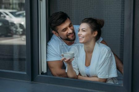 Photo pour Portrait de jeune couple heureux et aimant conversant et prenant un café dans la fenêtre - image libre de droit