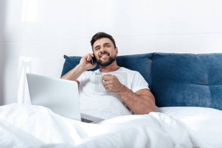 Young man talking on phone in bed
