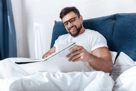 man reading magazine in bed