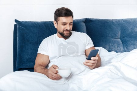 Young man using smartphone in bed