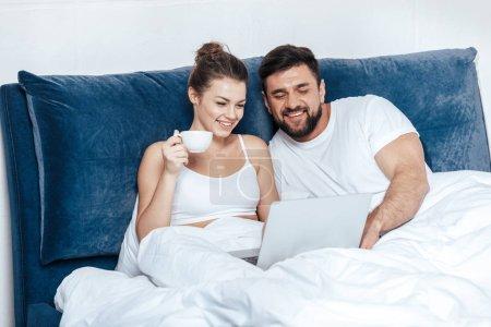 Foto de Retrato de joven mujer tomando café y el uso de ordenador portátil con su novio en la cama - Imagen libre de derechos