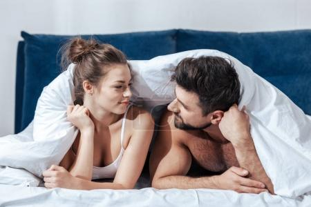Photo for Portrait of young happy loving couple under blanket in bed - Royalty Free Image