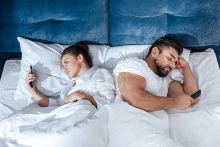 couple using smartphones in bed
