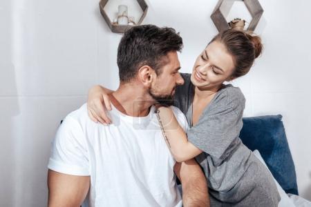 Photo pour Portrait de jeune couple amoureux embrasser au lit - image libre de droit