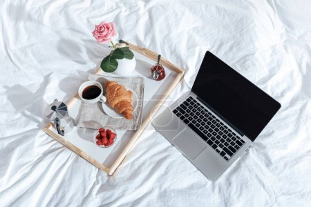 Tray with breakfast and laptop