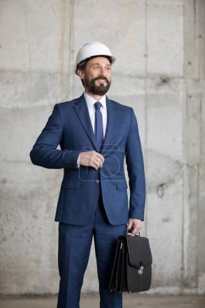 Photo pour Ingénieur au casque tenant porte-documents et regarder loin de sourire - image libre de droit