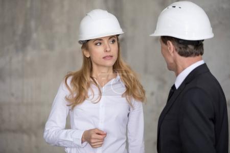 Photo pour Ingénieur blonde sérieux en casque dur regardant un collègue sur le chantier de construction - image libre de droit