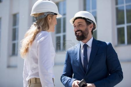 Photo for Businessman and businesswoman in hard hats talking and smiling each other outdoors - Royalty Free Image