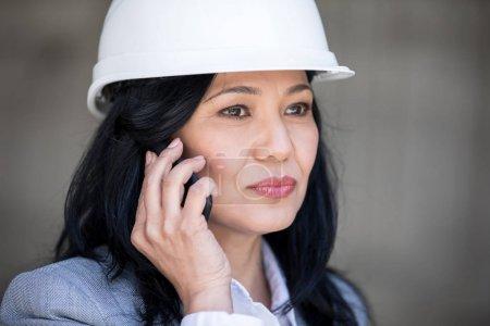 Photo pour Femme d'affaires âgé moyen confiant dans un casque parler sur smartphone et à la recherche de suite - image libre de droit