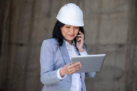 Photo pour Femme d'affaires ans milieu professionnel dans un casque parler sur smartphone et à l'aide de tablette numérique - image libre de droit