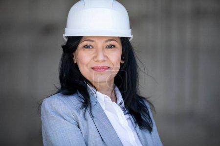 Photo pour Belle femme asiatique mature dans un casque, souriant à la caméra - image libre de droit