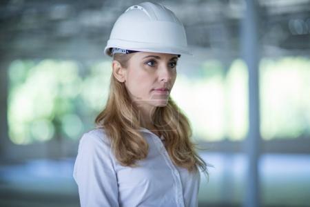 Photo pour Portrait de songeur architecte blonde dans un casque permanent et en regardant loin de travail - image libre de droit