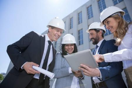 Photo for Low angle view of professional team of architects using digital tablet while working together - Royalty Free Image