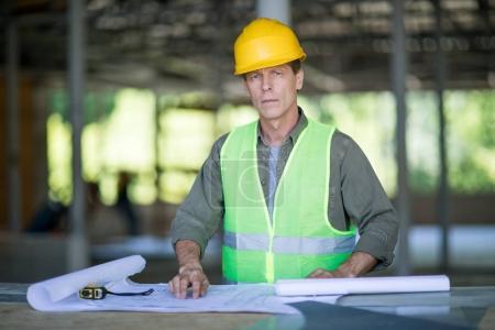 Photo pour Ingénieur sérieux dans un casque avec plans de travail et en regardant la caméra - image libre de droit