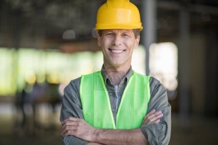 Photo pour Architecte professionnel mature en tenue de travail protectrice debout avec les bras croisés et souriant à la caméra - image libre de droit