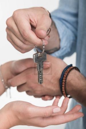 Photo pour Recadrée tir du jeune couple main dans la main avec des clés de la maison neuve - image libre de droit