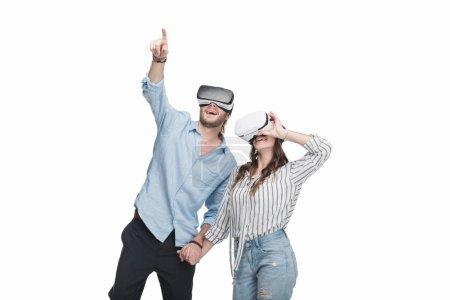 Photo pour Heureux jeune couple portant des casques de réalité virtuelle et main dans la main isolé sur blanc - image libre de droit