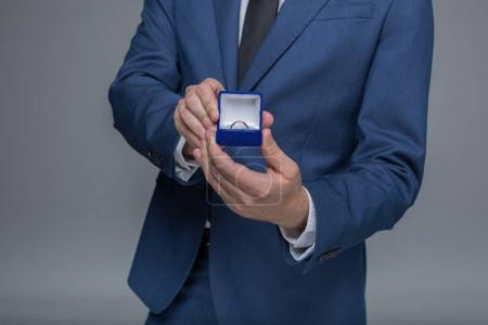 Photo for Cropped shot of stylish man in suit holding golden wedding ring in box - Royalty Free Image