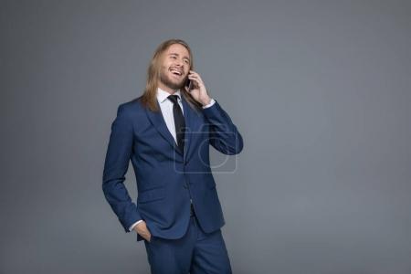 smiling caucasian businessman talking on smartphone