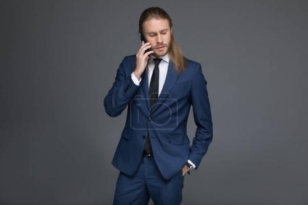 pensive caucasian businessman talking on smartphone