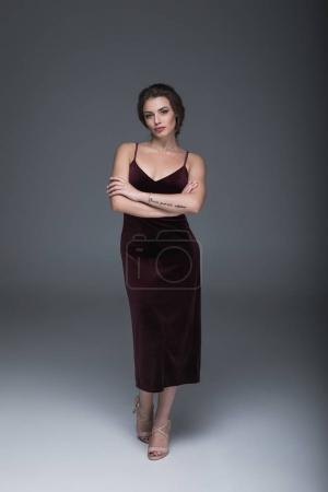 Photo for Beautiful caucasian woman in evening dress looking at camera with arms crossed - Royalty Free Image