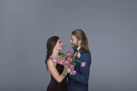 sweethearts in evening outfit holding peonies