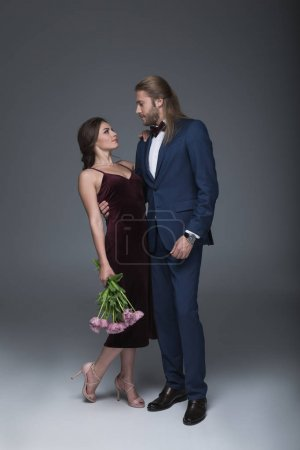 Photo pour Jeunes amoureux élégant en soirée debout tenue fashion avec bouquet de fleurs - image libre de droit