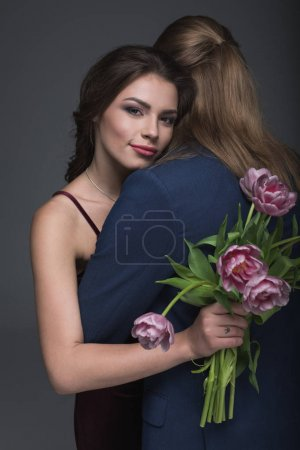 woman embracing boyfriend with bouquet of peonies