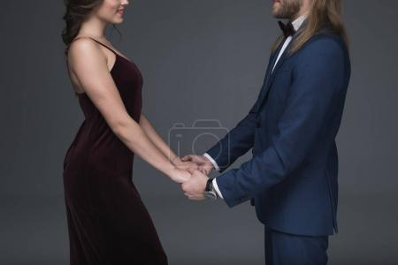 sweethearts in formal wear holding hands