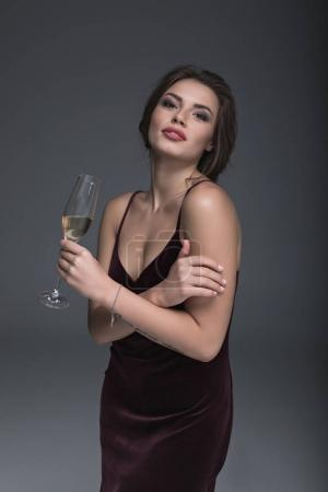 Photo for Young lady in evening dress holding glass of champagne and looking at camera - Royalty Free Image