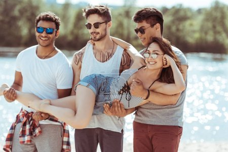 Photo for Three multiethnic men holding attractive asian girl on hands - Royalty Free Image