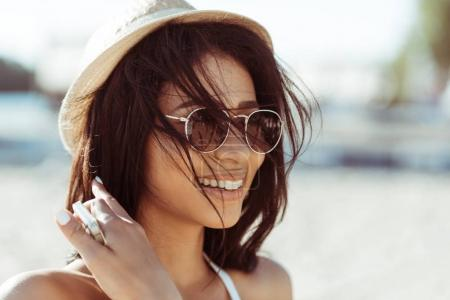 Photo for Close-up portrait of beautiful brunette girl in sunglasses and straw hat looking away at beach - Royalty Free Image