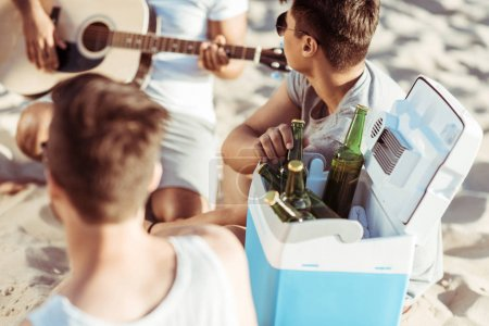 Friends drinking beer at beach