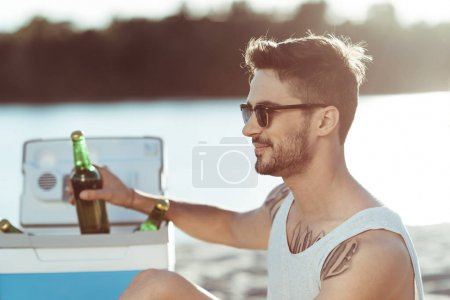 Man drinking beer at beach