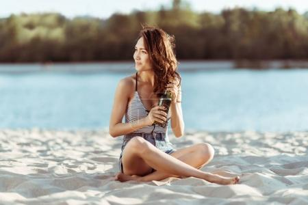 Woman drinking beer on beach
