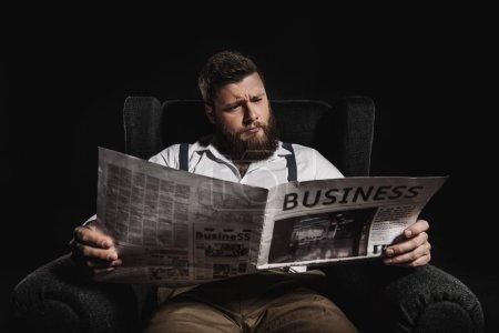 Photo pour Homme à la mode, lire le journal d'affaires tout en étant assis dans le fauteuil isolée sur fond noir - image libre de droit