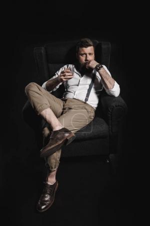 stylish man holding whisky glass