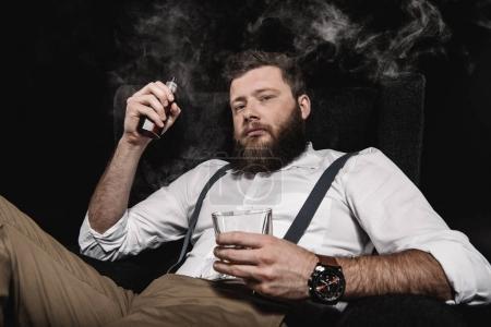 Photo pour Homme élégant en chemise blanche et bretelles vapotage et tenant verre de whisky, isolé sur noir - image libre de droit