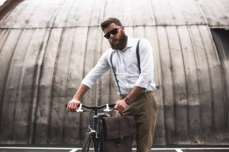 stylish man standing with bicycle