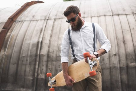 Photo for Stylish bearded man in sunglasses and suspenders holding longboard - Royalty Free Image