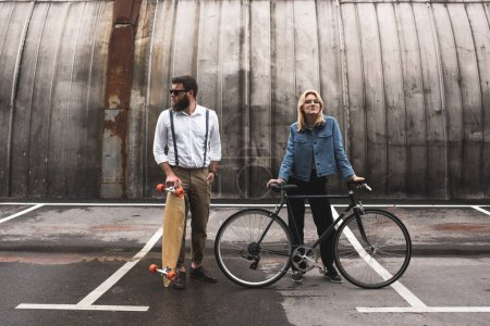Photo for Stylish young couple standing with bicycle and longboard on parking place - Royalty Free Image