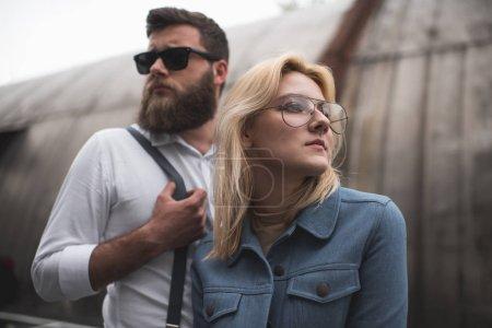 Photo pour Élégant jeune couple posant dans les lunettes et lunettes de soleil et la recherche. - image libre de droit