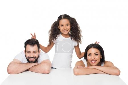 Photo for Adorable smiling girl making horns gesture behind heads of happy parents - Royalty Free Image