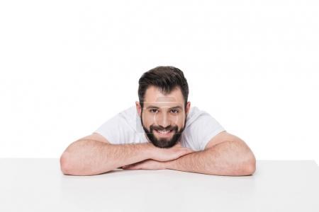 Photo pour Beau jeune homme barbu appuyé au tableau blanc et souriant à la caméra - image libre de droit