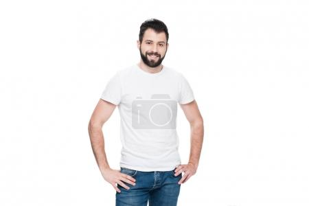 Bearded young man in white t-shirt standing with h...