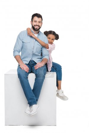 father and daughter sitting on cube