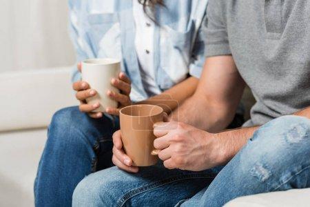 Photo pour Vue recadrée du jeune couple buvant du café à la maison - image libre de droit