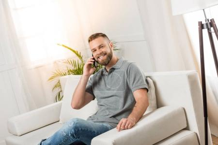 Photo for Young smiling man using smartphone and sitting on sofa at home - Royalty Free Image