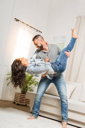 Photo for Young smiling man holding excited woman in his arms at home - Royalty Free Image